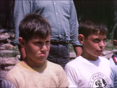 stockvideo's en b-roll-footage met 1964 close up two young boys standing still outdoors / start looking around smiling / summer camp - 1964