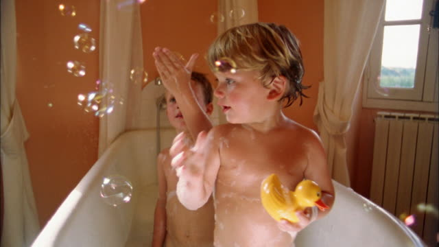 Close up two young boys trying to catch bubbles while in bathtub / boy playing w/rubber duck