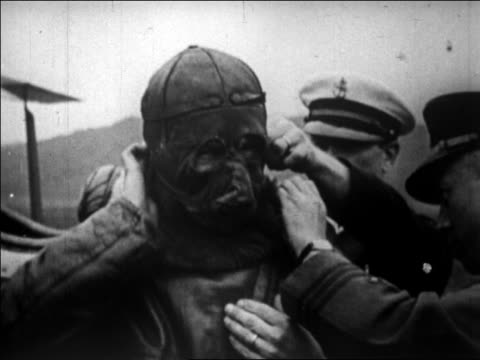 b/w 1929 close up uniformed men helping pilot put on oxygen mask for high elevation flight / washington dc - oxygen mask stock videos & royalty-free footage