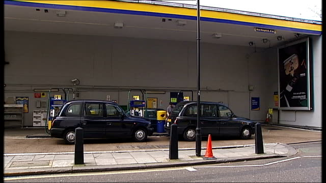close up 'unleaded' sign on petrol pump taxis on garage forecourt next to petrol pumps back view man filling taxi with petrol as standing next to... - unleaded stock videos and b-roll footage