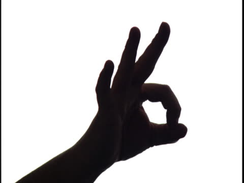 close up up of a hand flashing an okay sign silhouetted against white