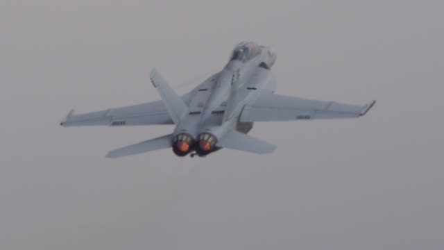 close up us f-18 hornet military jet accelerates away from camera, afterburner exhaust flaming. - afterburner stock videos and b-roll footage
