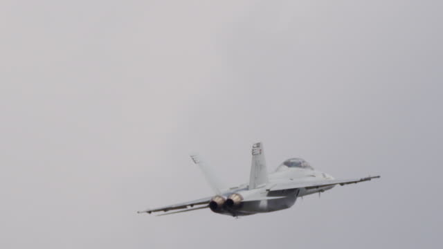 Close up US F-18 Hornet military jet flying away from camera.
