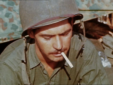 WWII close up US Marine smoking cigarette while typing in the field / Philippines