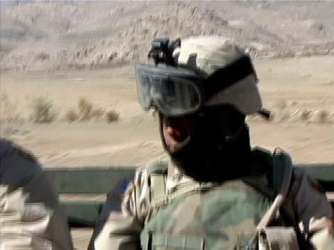 Close up US soldier riding through desert on back of truck/ Afghanistan