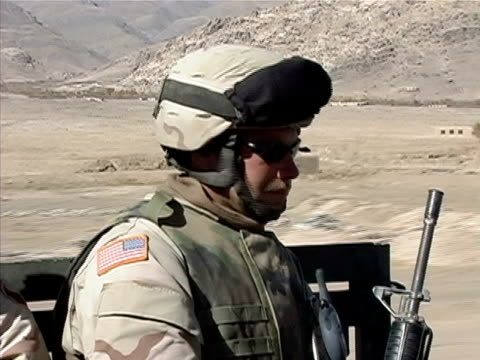 close up us soldier riding through desert on back of truck/ afghanistan - operazione enduring freedom video stock e b–roll