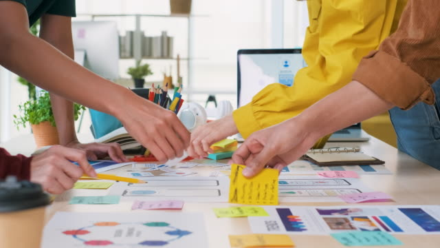 close up ux developer and ui designer hand brainstorming about mobile app interface wireframe design on table color code at modern office.creative digital development agency.panning out - professione creativa video stock e b–roll