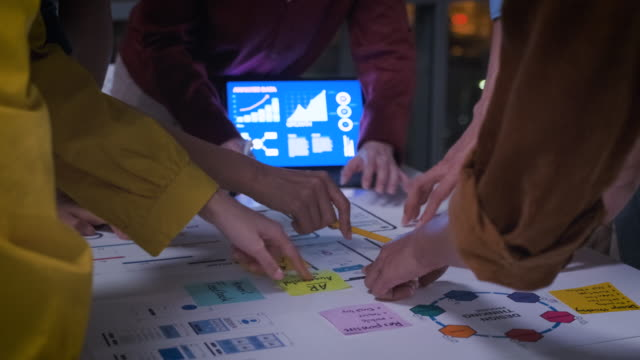 close up ux developer and ui designer hand brainstorming about mobile app interface wireframe prototype design on table in modern office at night.working late of creative digital development agency - deadline stock videos & royalty-free footage