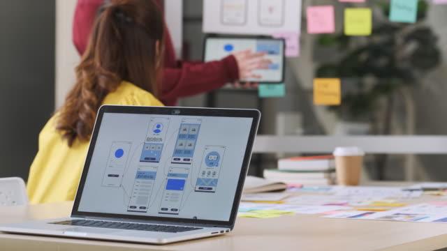 アジアの開発者とデザイナーがモダンオフィスでの会議でホワイトボード上のインターフェイスを提示しながら、ラップトップ上のux / uiデザインをクローズアップ。クリエイティブデジタル - プロトタイプ点の映像素材/bロール