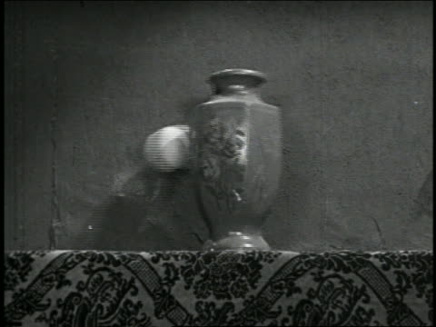 b/w 1928 close up vase on mantle getting hit by baseball + falling / short - vase stock videos & royalty-free footage