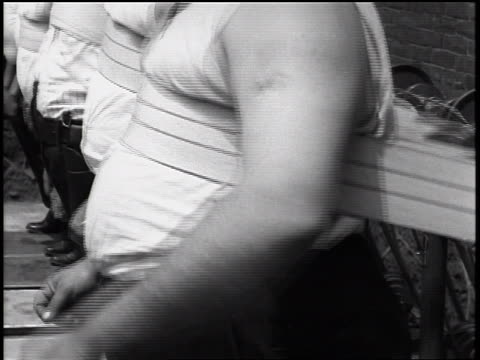 b/w 1935 close up vibrating straps on bellies of policemen in tank tops / newsreel - overweight active stock videos & royalty-free footage