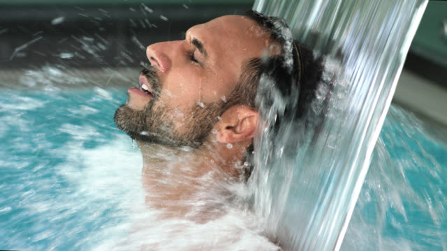 hotel day spa indoor pool with thermal spring water torrent shower – attractive sporty buff tanned sexy man in his 30s with short dark hair and trimmed black beard enjoys the massaging splashing foaming waters after sauna and treatments - masculinity male - masculinity stock videos & royalty-free footage