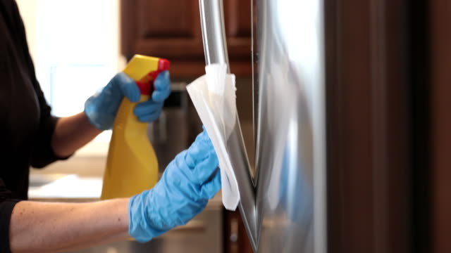 4k close up video of a woman wearing disposable gloves as she cleans a stainless steel refrigerator handle with a disinfectant wipe and cleaning product - rubbing stock videos & royalty-free footage
