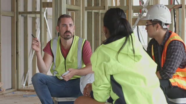 Close up video of builder talking with his colleagues on the coffee break at construction site