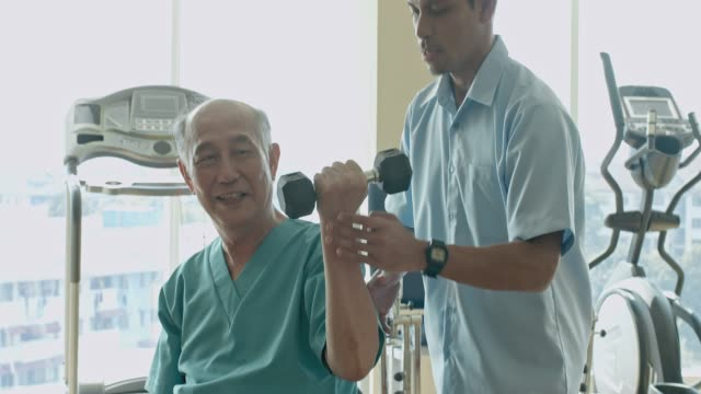 Close up video of Chinese senior man lifting hand weight at recovery