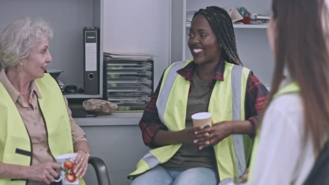 Close up video of three diverse women colleagues at warehouse having the coffee break