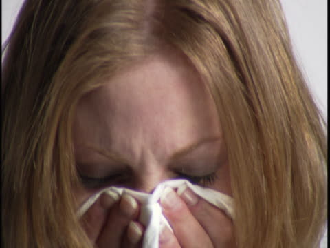 close up video portrait of a sick young woman as she sneezes and look miserable - sneezing stock videos & royalty-free footage
