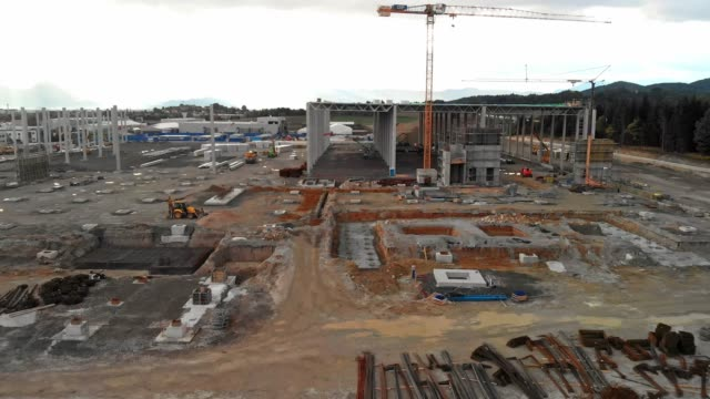 close up view, drone flying over massive hangar construction site - crane construction machinery stock videos & royalty-free footage