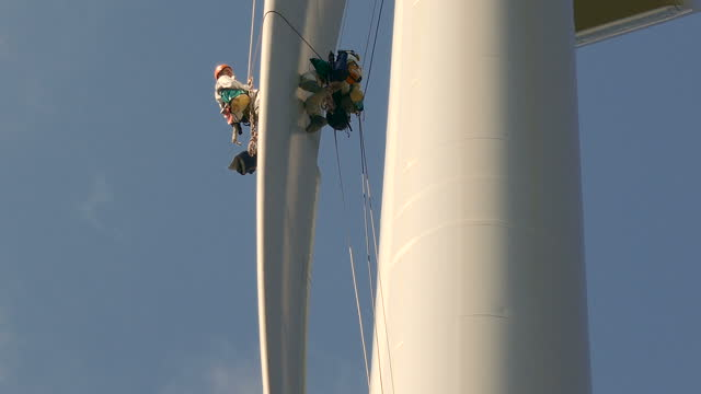close up view from bottom on wind-turbine and two rope access technicians - industrial climbers rappelling down around blade on the ropes, doing inspection, clear sky and sunny day. tower behind them. - safety harness stock videos & royalty-free footage