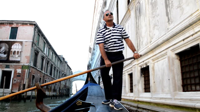 Close up view of a gondolier riding his gondola in canals during a hot summer day