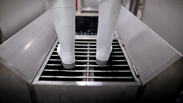 close up view of a worker in sterile cloths washing boots before working. hygiene at food factory - infectious disease stock videos & royalty-free footage