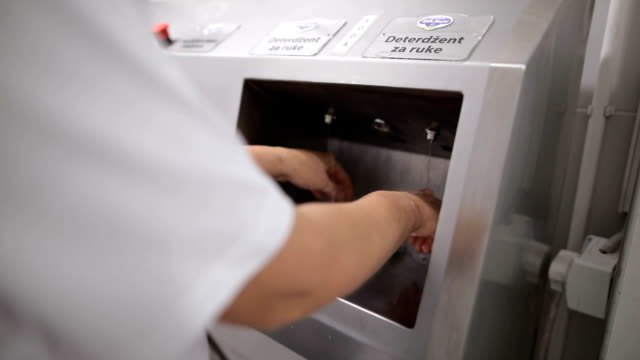 close up view of a worker in sterile cloths washing hands before working.hand hygiene at food factory - infectious disease stock videos & royalty-free footage