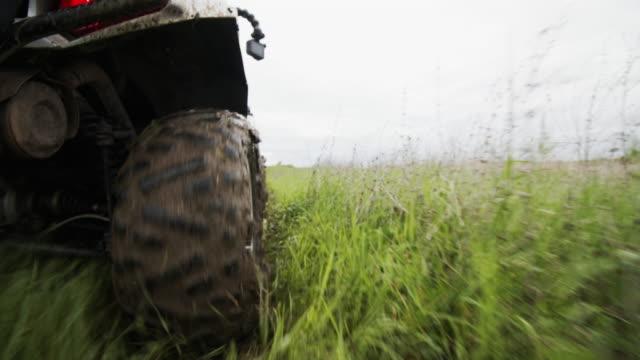 vidéos et rushes de fermez-vous vers le haut des roues d'atv dans le terrain - sports utility vehicle