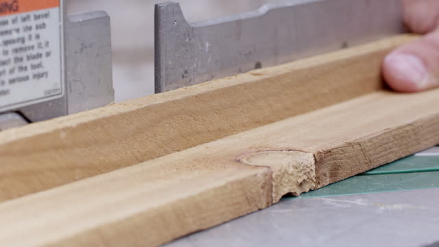 close up view of board being cut by miter saw at an angle - おがくず点の映像素材/bロール