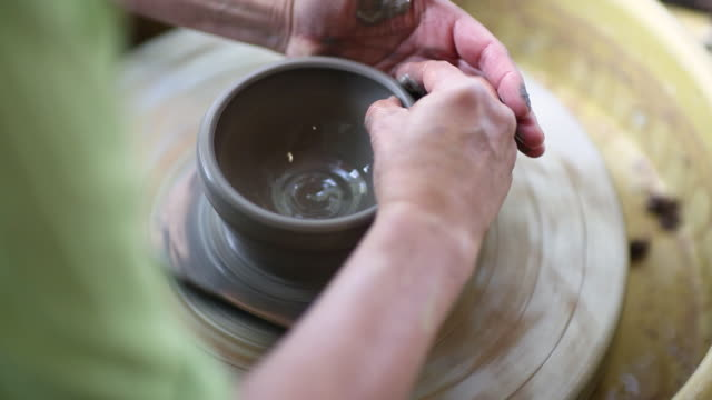 close up view of female potter using her hands to make a small clay pot - potter stock videos & royalty-free footage
