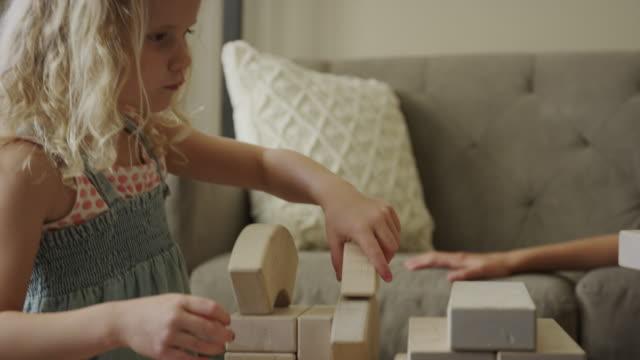 close up view of girls playing with building blocks / orem, utah, united states - orem bildbanksvideor och videomaterial från bakom kulisserna
