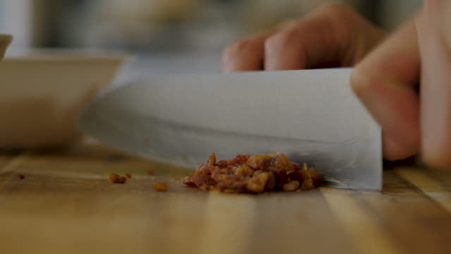 close up view of hand chopping crispy bacon on wooden cutting board - chopping stock videos & royalty-free footage