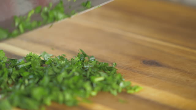 close up view of hand chopping fresh parsley in the kitchen - parsley stock videos and b-roll footage