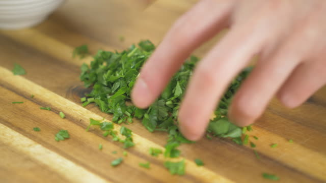 close up view of hand picking fine chopped fresh parsley in the kitchen - parsley stock videos and b-roll footage