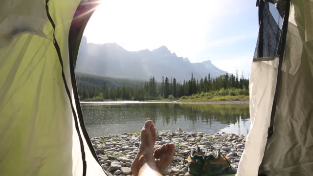 close up view of hiker's feet at tent door, river and mountains behind - camping stock videos & royalty-free footage