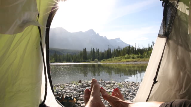close up view of hikers' feet at tent door, river and mountains behind - tenda video stock e b–roll