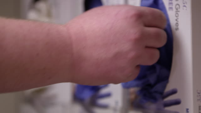 close up view of person pullng rubber gloves out of box - rubber glove stock videos & royalty-free footage
