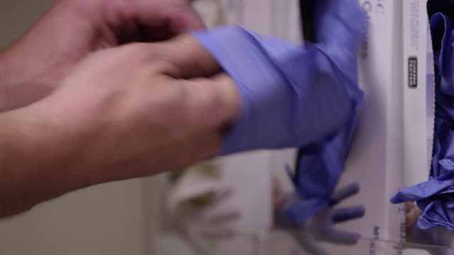 close up view of person putting on rubber gloves - latex glove stock videos & royalty-free footage