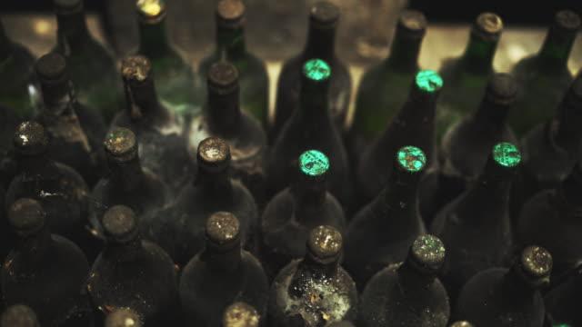 vídeos de stock, filmes e b-roll de vista de perto da pilha de velhas garrafas de vinho empoeiradas na adega - garrafa