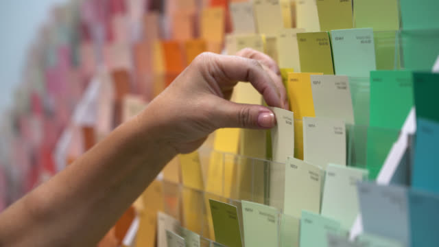 close up view of unrecognisable female customer choosing a color sample at a paint shop - scegliere video stock e b–roll