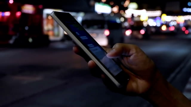 Close up view of woman hand that writing message on her smartphone against evening road with cars light background.Woman using cellphone and waiting for taxi