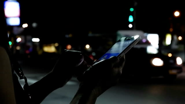 close up view of woman hand that writing message on her smartphone against evening road with cars light background.woman using cellphone and waiting for taxi - finding stock videos & royalty-free footage