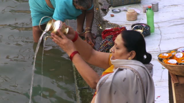 Close up view of woman pouring holy water into ganges river