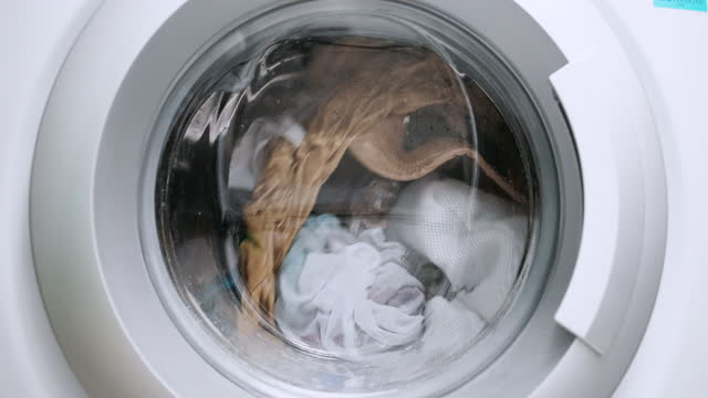 close up view porthole of washing machine. washing clothes process in slow motion - washing machine stock videos & royalty-free footage