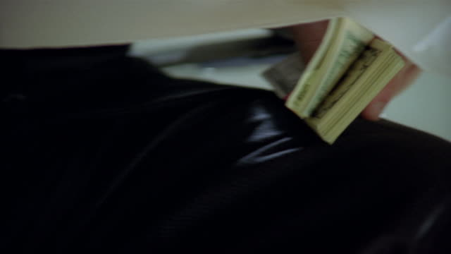close up view under table of businessman passing bundle of money to another businessman - table stock videos & royalty-free footage