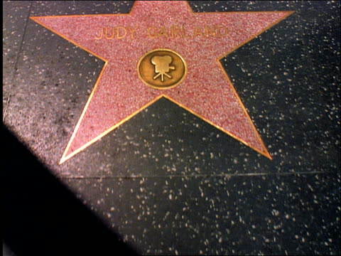 close up walking point of view of Hollywood's Walk of Fame / Judy Garland's name