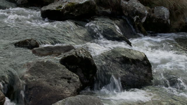 Close up water flowing over rocks and boulders in a small mountain stream, Brecon Beacons, Wales