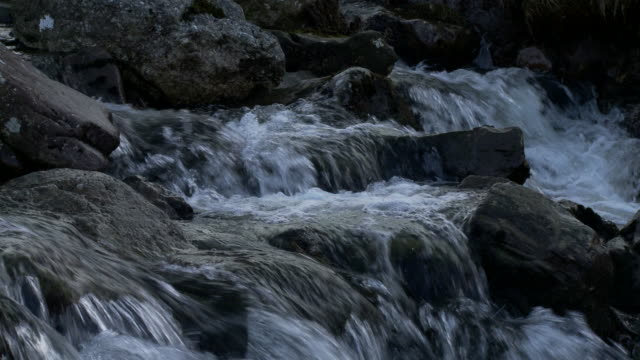 Close up water flowing over rocks and boulders in mountain stream, Brecon Beacons, Wales