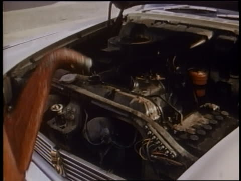 1958 close up watering can pouring water into car radiator - 注ぎ口点の映像素材/bロール