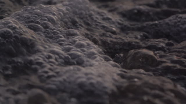 stockvideo's en b-roll-footage met close-up van wave op strand super slow motion - stromend water