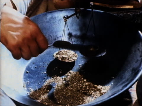 1965 close up weighing gold particles w/spoon and balance / 'the gold rush' / audio - waage gewichtsmessinstrument stock-videos und b-roll-filmmaterial